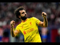 Liverpool's Mohamed Salah celebrates after scoring a penalty during the Champions League Group B  match between Atletico Madrid and Liverpool at Wanda Metropolitano stadium in Madrid, Spain yesterday.