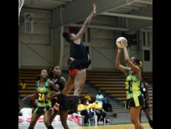 Trinidad and Tobago's goalkeeper Shaquanda Green-Noel leaps to block a shot by Jamaica's Gezelle Allison during last night's game two of the three-Test Sunshine Netball Series at the National Indoor Sports Centre.