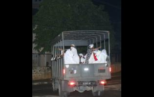 Members of the Pathways International Kingdom Restoration Ministries in Montego Bay, St James, being taken away in a Jamaica Defence Force vehicle on Sunday.