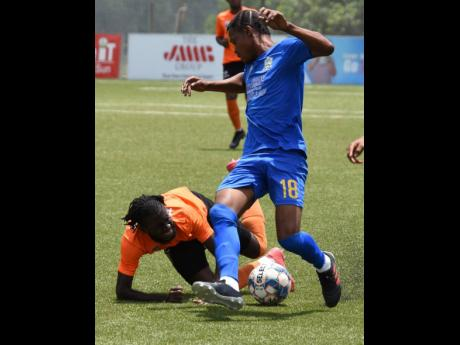 Devroy Grey (left) of Tivoli Gardens goes down after a tackle by Oniel Small (right) of Molynes United during their Jamaica Premier League match at the UWI-JFF Captain Horace Burrell Centre of Excellence last Saturday. The match ended 1-1.