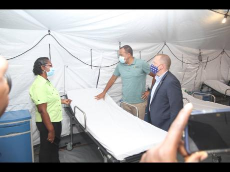 Eugena Clarke-James, acting CEO of May Pen Hospital, speaks with health minister Dr Christopher Tufton (centre) and  John McIntyre, chargé d'Affaires at the US Embassy in Kingston, following Wednesday's official opening of the 40-bed field hospital.